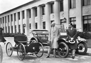 "Henry Ford standing by the first car he made called ""The Quadricycle"" and the fifteenth million Model T manufactured by his company."